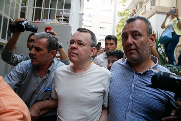 American Pastor Andrew Craig Brunson (center) was placed under house arrest due to unspecified health problems