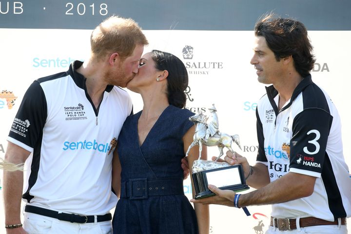 Nacho Figuares of presents the Sentebale Polo 2018 trophy as Meghan, Duchess of Sussex and Prince Harry, Duke of Sussex, kiss.