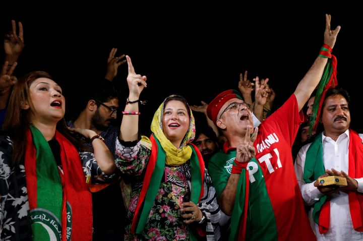 Supporters of Imran Khan, chairman of Pakistan Tehreek-e-Insaf (PTI), gesture to party songs, as they celebrate a day after t