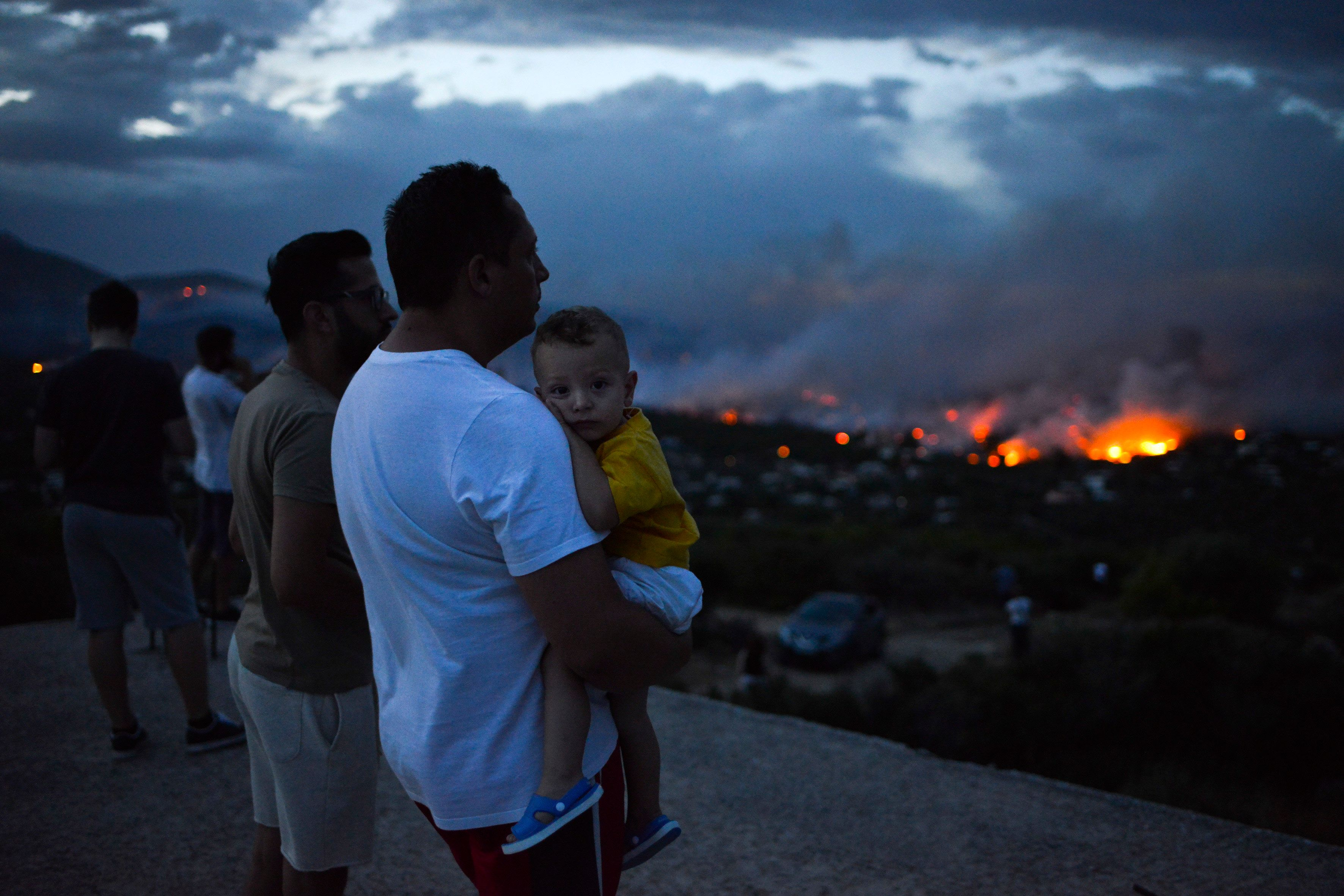 A man holds his son as a wildfire burns in the town of Rafina, near Athens, on July 23, 2018.