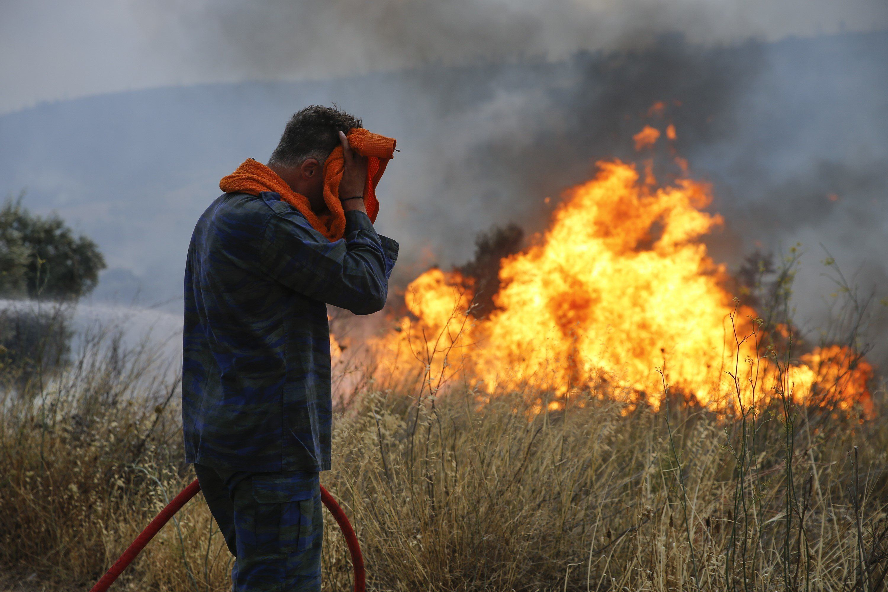 ATHENS, GREECE - JULY 23: Firefighters and volunteers try to extinguish the fire broke out  at forested land in Penteli town of Athens, Greece on July 23, 2018. (Photo by Ayhan Mehmet/Anadolu Agency/Getty Images)