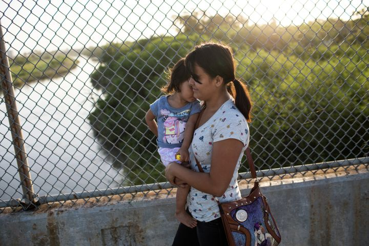 A Honduran woman holds her 2-year-old daughter as they wait on the Mexican side of theinternational bridge at Brownsvil