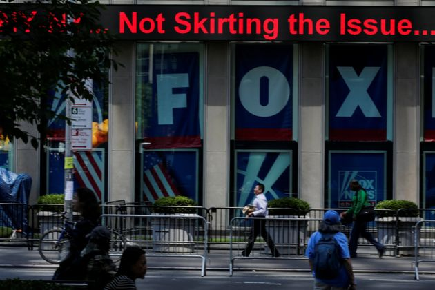 People pass by ads for Fox News at the News Corporation building in New York City in