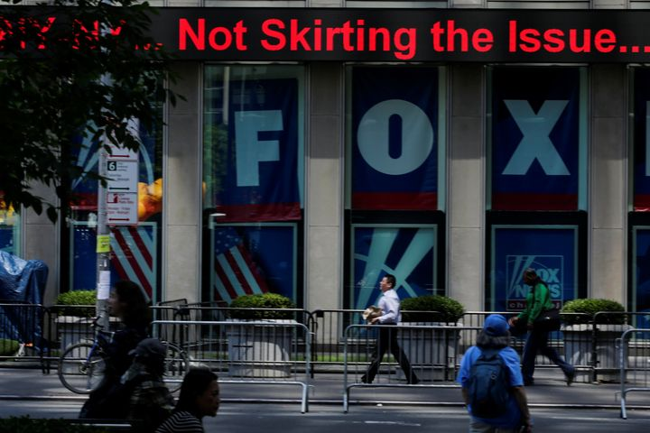People pass by ads for Fox News at the News Corporation building in New York City in June.