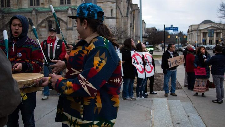 A group of men sing and drum on the steps of Kalamazoo City Hall in March, before the city commission voted to remove the Fou