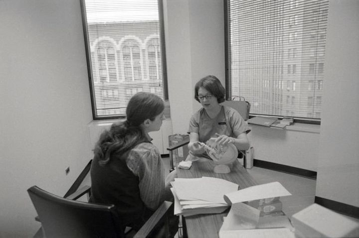 In a New York City abortion clinic in 1971, a patient is shown a model of the female reproductive system by a clinic member.&