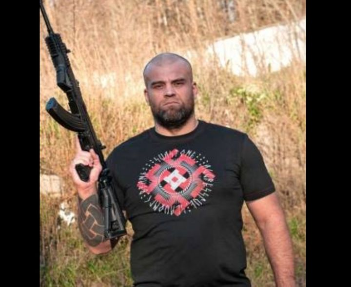 A post from Sva Stone's Facebook page shows a man modeling one of its Nazi-inspired T-shirts while holding a gun.