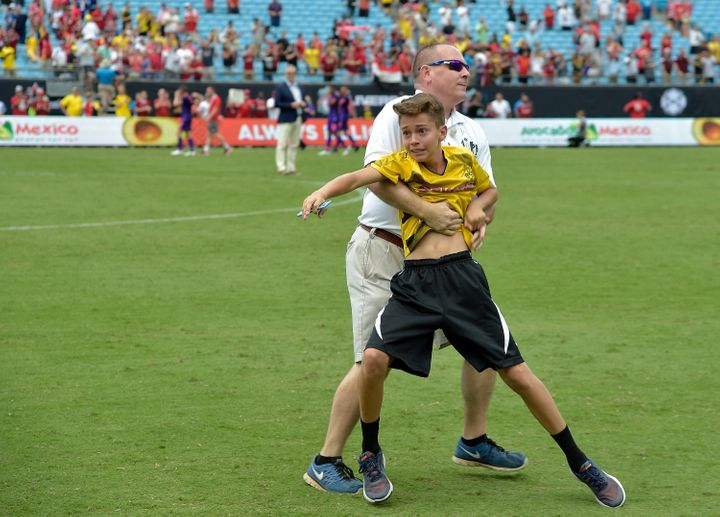 A young fan is stopped by security as hetries to talk to Christian Pulisic of Borussia Dortmund after an International
