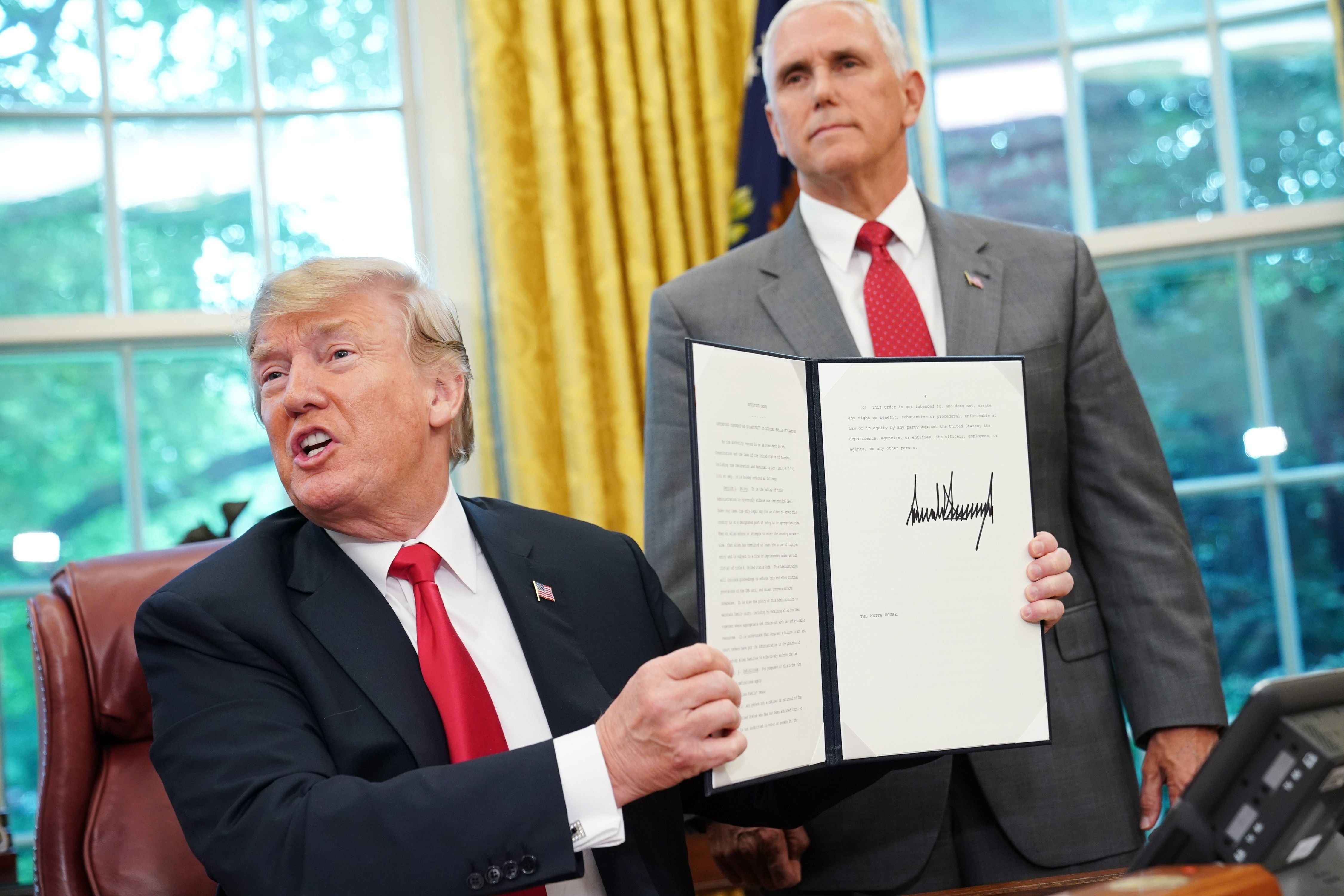 TOPSHOT - Watched by Vice President Mike Pence, US President Donald Trump shows an executive order on immigration which he just signed in the Oval Office of the White House on June 20, 2018 in Washington, DC. - US President Donald Trump on Wednesday signed an executive order aimed at putting an end to the controversial separation of migrant families at the border, reversing a harsh practice that had earned international scorn.'It's about keeping families together,' Trump said at the signing ceremony. 'I did not like the sight of families being separated,' he added. (Photo by Mandel Ngan / AFP)        (Photo credit should read MANDEL NGAN/AFP/Getty Images)
