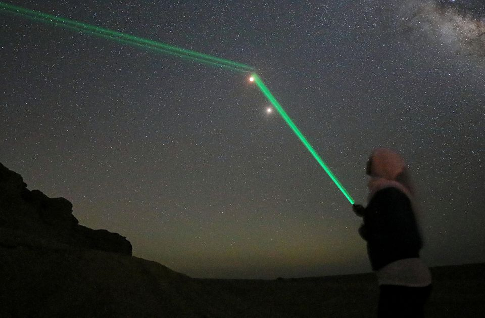 People shine laser lights toward the moon in the desert of Al Fayoum Governorate, southwest of
