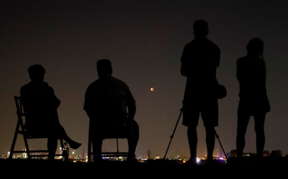 People in a field watch the moon over the skyline of Frankfurt,