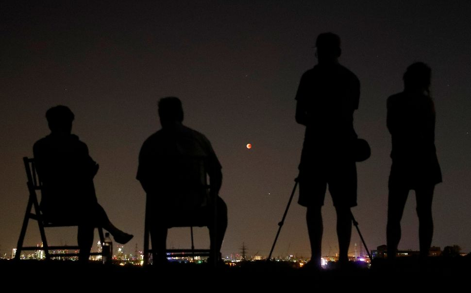 People in a field watch the moon over the skyline of Frankfurt, Germany.