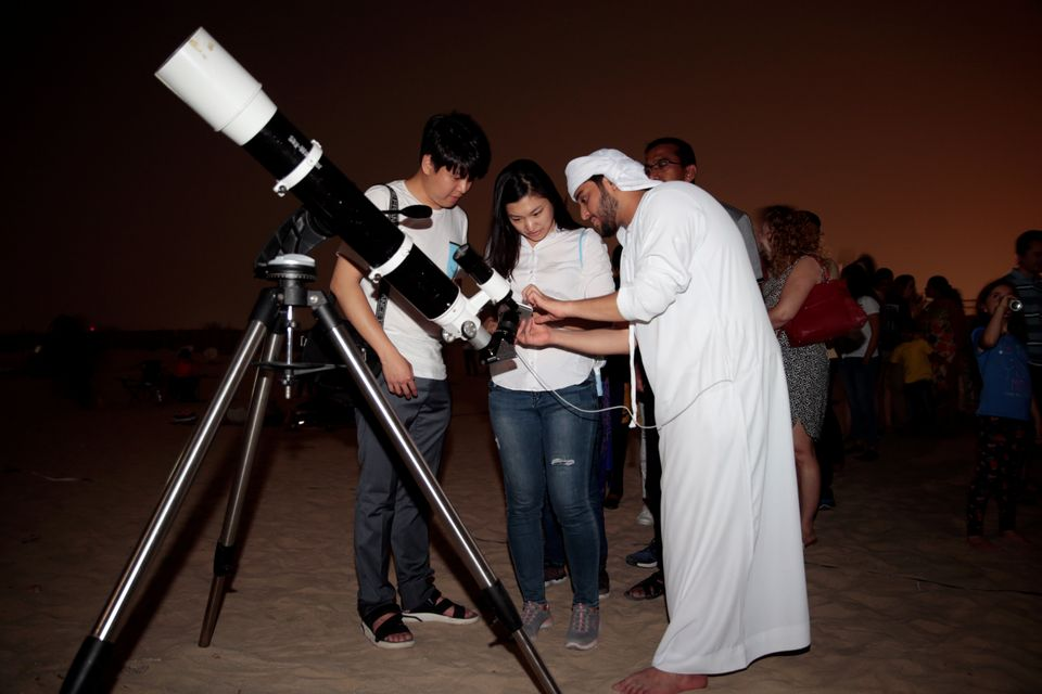 An Emirati man uses a telescope to take a picture of the lunar eclipse of a full