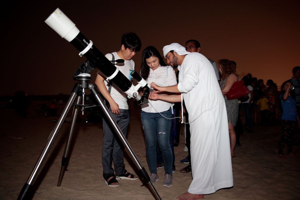 "An Emirati man uses a telescope to take a picture of the lunar eclipse of a full ""Blood Moon"" at Al Sadeem Observatory in Al"