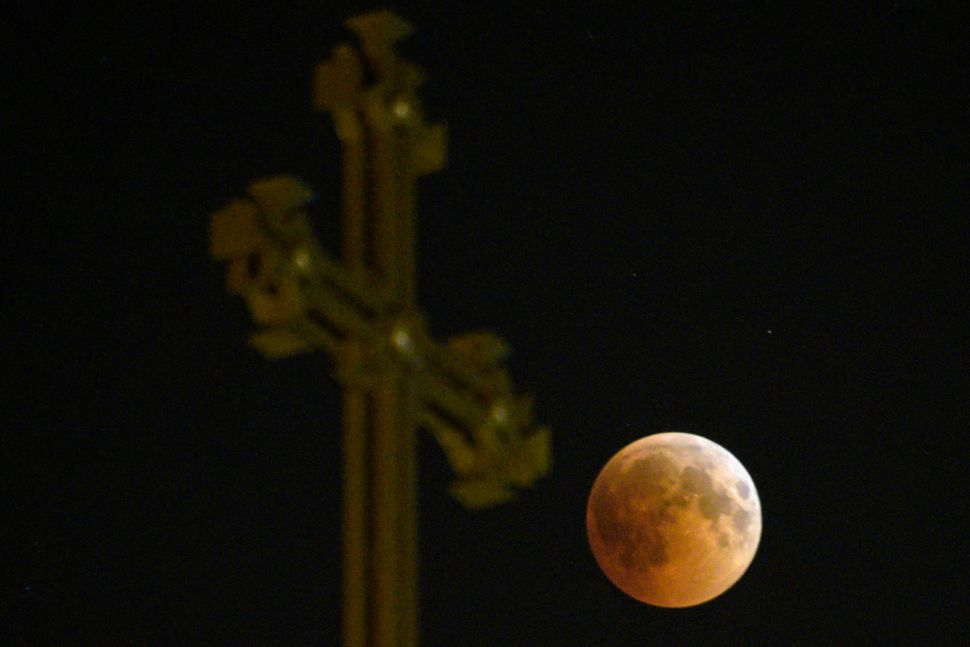 The moon passes over an Armenian Apostolic Church cathedral in Yerevan.