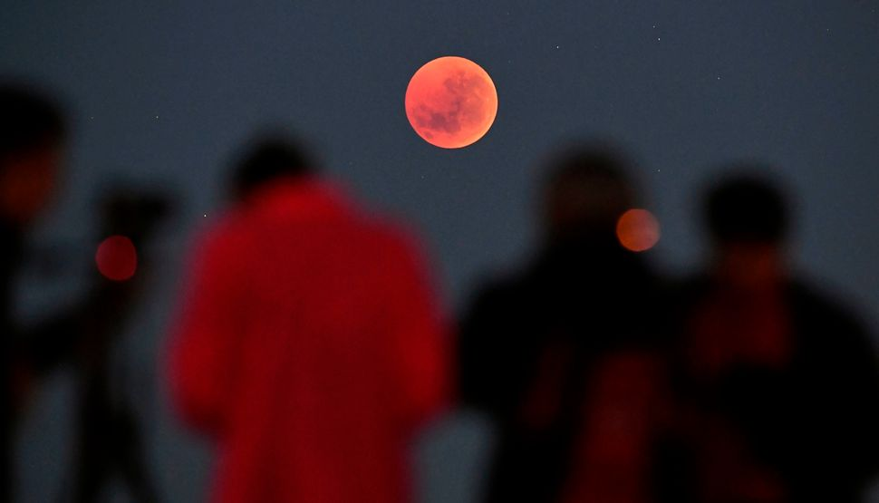 People gather to watch the moon in Melbourne, Australia.