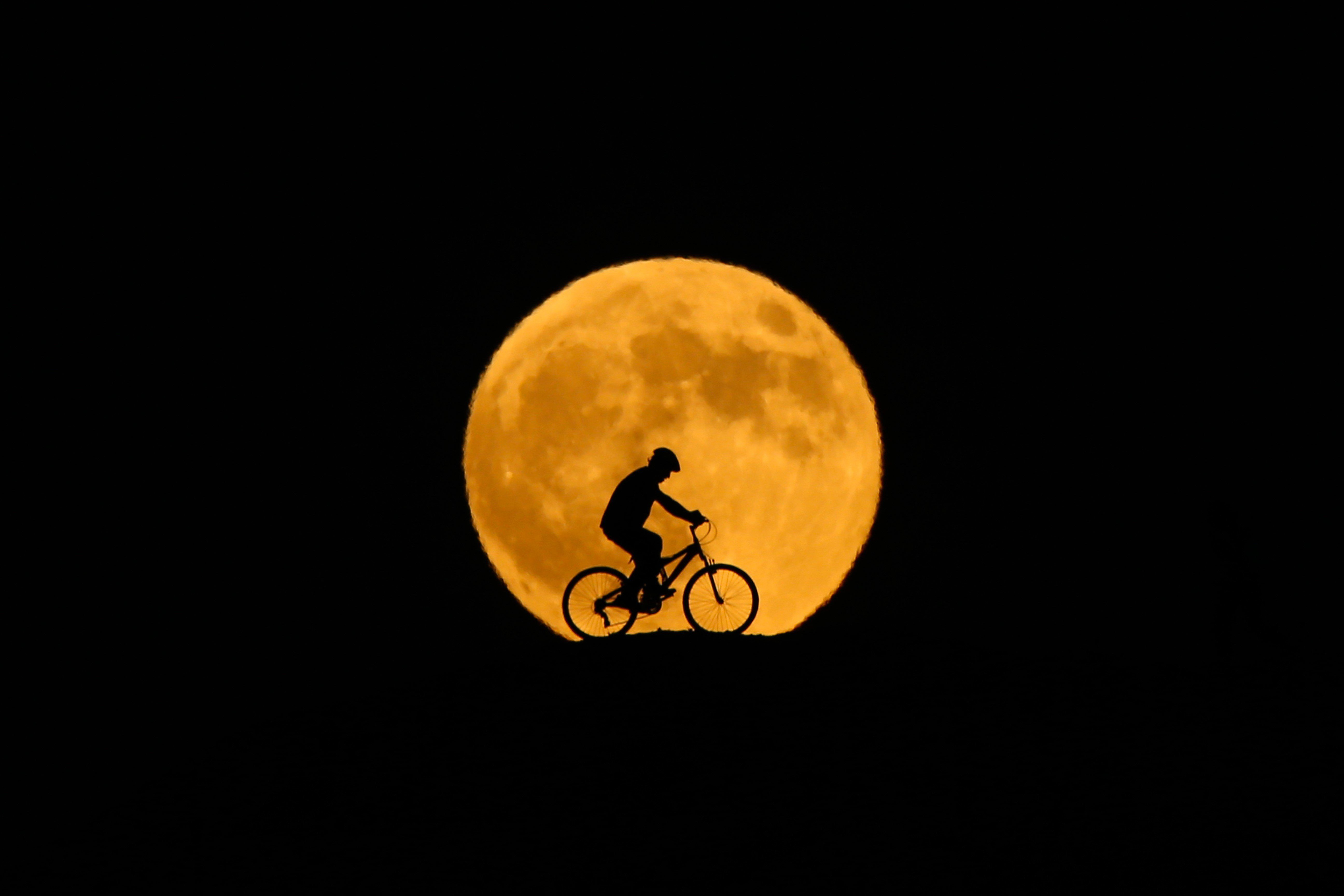 VAN, TURKEY - JULY 27: The full moon rises behind silhouette of a man riding a bicycle prior to the totally phase of Century's longest ''Blood Moon'' eclipse in Van, Turkey on July 27, 2018. (Photo by Ozkan Bilgin/Anadolu Agency/Getty Images)