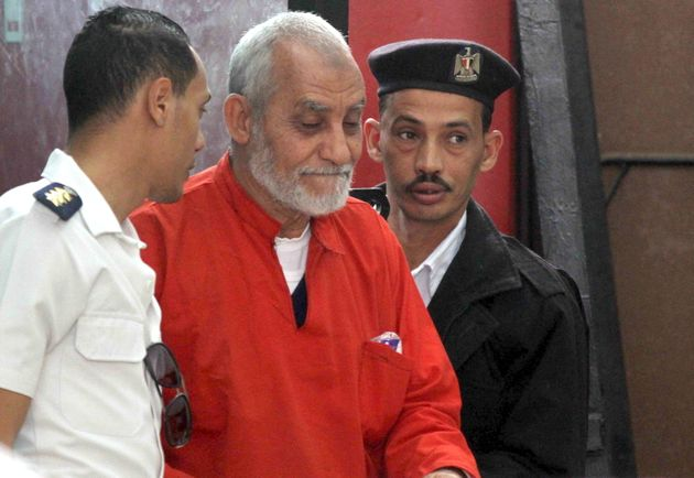 Mohamed Badie, top leader of Egypt's outlawed Muslim Brotherhood, is led by police to talk during a trial...