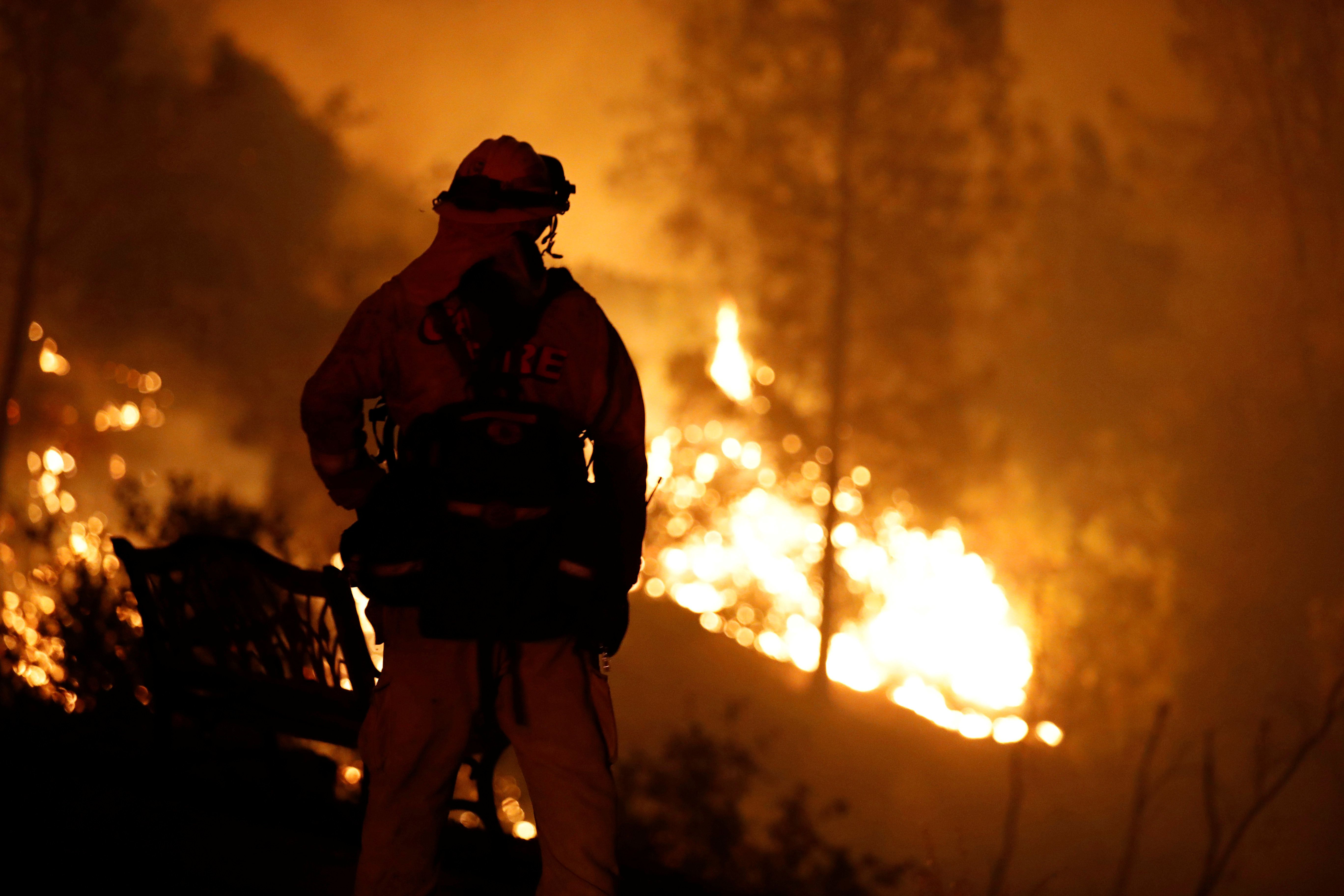 A firefighter watches flames advance up a hill towards homes as crews battle the Carr Fire, west of Redding, California, U.S. July 27, 2018.  REUTERS/Fred Greaves