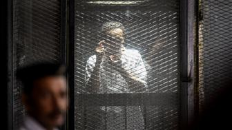 TOPSHOT - Egyptian photojournalist Mahmoud Abdel Shakour Abouzied, also known as Shawkan, makes a gesture mimicking taking a photograph from inside a soundproof glass dock, during his trial in the capital Cairo on July 28, 2018. - Shawkan, who in May received UNESCO's Press Freedom Prize, is among 713 defendants on trial for killing policemen and vandalising property during 2013 clashes between security forces and supporters of ousted Islamist president Mohamed Morsi. The court postponed a verdict on his and other cases. (Photo by Khaled DESOUKI / AFP)        (Photo credit should read KHALED DESOUKI/AFP/Getty Images)
