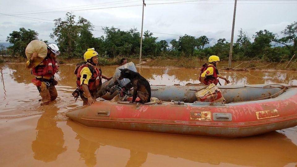 28일 라오스 사남사이 바미아마을 초입에서 구조대원들이 개 한 마리를 구조해 배에 태운 채 나오고