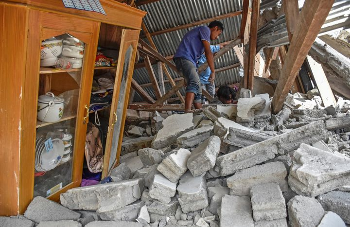 A villager walks through the ruins of a collapsed house followingthe earthquake at the Sembalun Selong village in Lombo