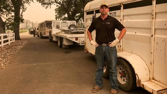 Tucker Zimmerman stands next to the trailer he has used to rescue scores of horses left behind in evacuated areas from the Carr fire in Shasta County, west of Redding, California, U.S.. July 28, 2018. Picture taken July 28, 2018.  REUTERS/Alexandria Sage