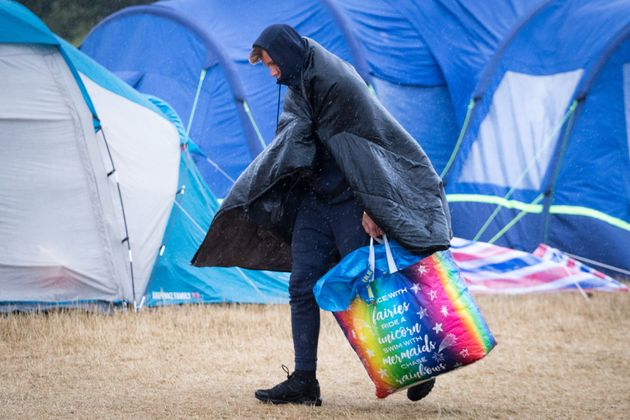 A festival goer walks in the wind and rain at Camp Bestival, at Lulworth Castle, on