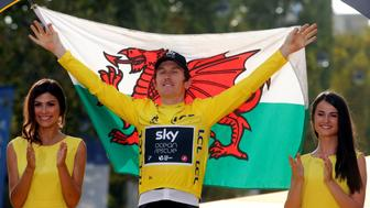 Cycling - Tour de France - The 116-km Stage 21 from Houilles to Paris Champs-Elysees - July 29, 2018 - Team Sky rider Geraint Thomas of Britain celebrates his overall victory on the podium with a Welsh flag. REUTERS/Philippe Wojazer