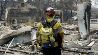 Capt Scott Fisher with the San Bernardino County Fire Department surveys a wildfire-damaged neighborhood Sunday July 29 2018 in Keswick Calif