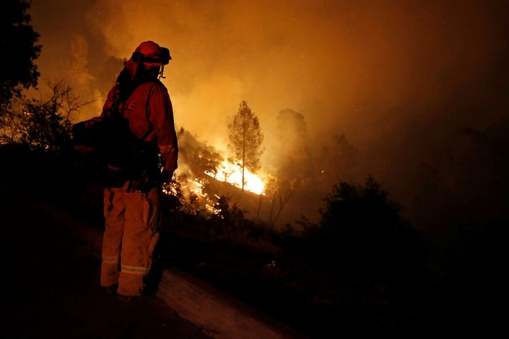 A firefighter watches flames advance up a hill towards homes as crews battle the Carr Fire, west of Redding, California.