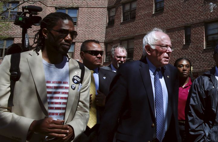 New York City Council member Jumaane Williams walks with then-presidential candidate Sen. Bernie Sanders through a housi