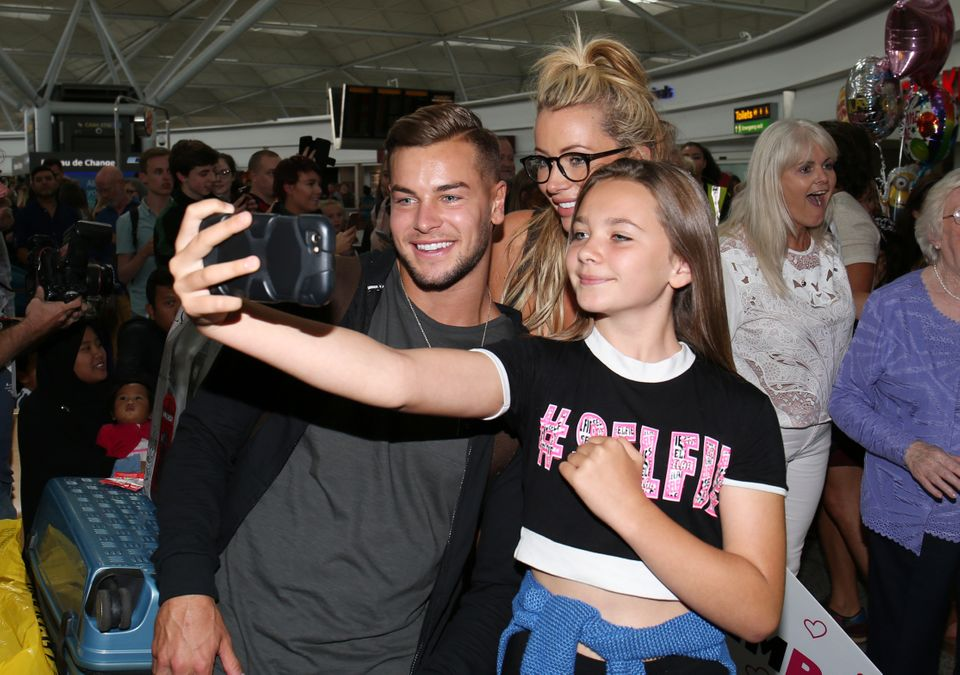 Chris Hughes and Olivia Attwood posing for photos at Stansted