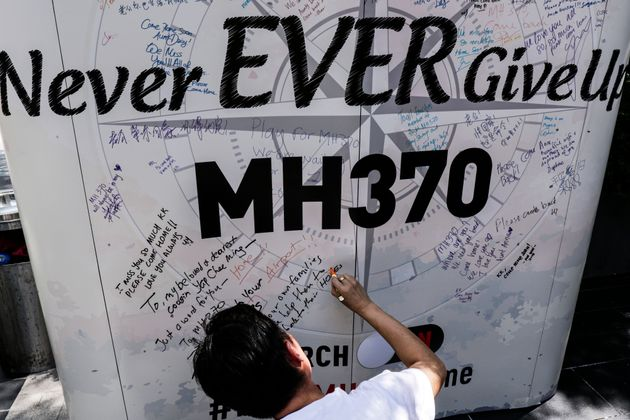 A man writes a message on a board onthe first anniversary of the missing Malaysian Airlines