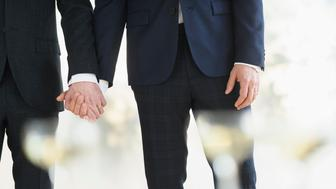 Caucasian gay grooms holding hands at wedding
