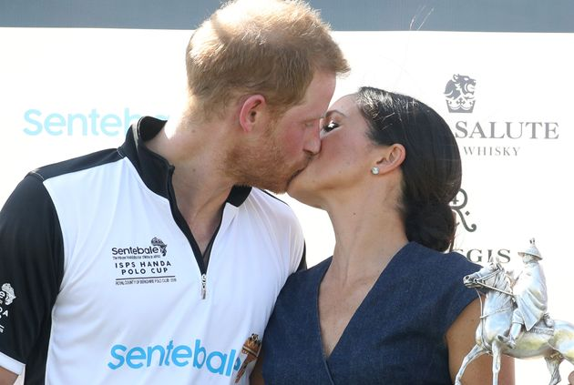 Meghan, Duchess of Sussex and Prince Harry kiss after posing with the trophy after the Sentebale Polo...