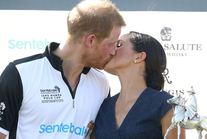 Meghan, Duchess of Sussex and Prince Harry kiss after posing with the trophy after the Sentebale Polo Cup on July 26 in Windsor, England.