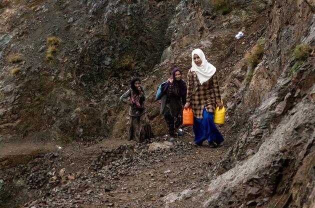 En novembre 2016, de jeunes filles portent l'eau d'une source à leur village, Tnerhourhine, près...