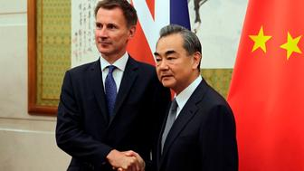 Britain's Foreign Secretary Jeremy Hunt (L) shakes hands with his Chinese counterpart Wang Yi as they pose for photographs before their meeting at the Diaoyutai State Guesthouse in Beijing on July 30, 2018. (Photo by Andy Wong / POOL / AFP)        (Photo credit should read ANDY WONG/AFP/Getty Images)