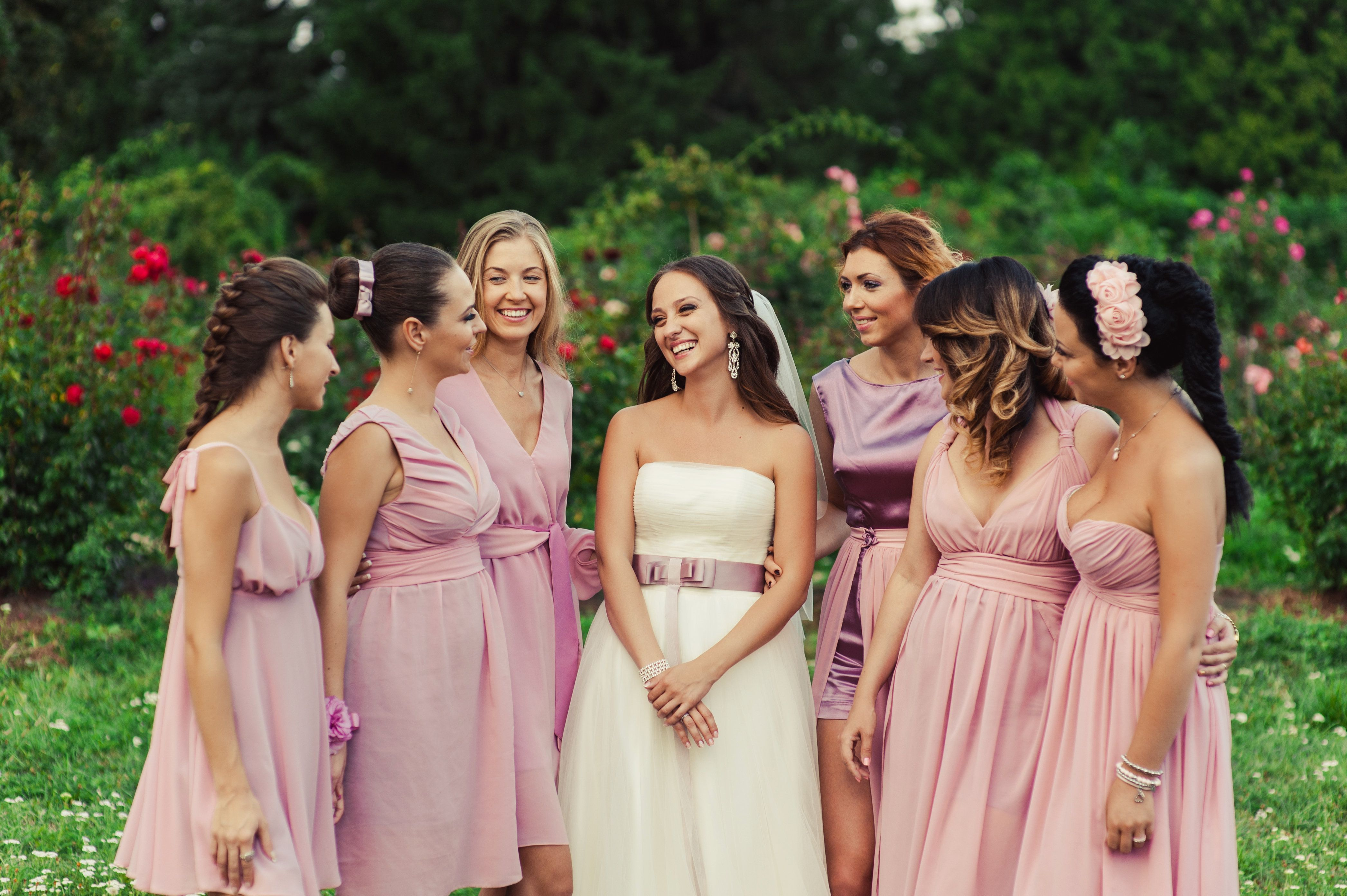 The bride with bridesmaids in pink dresses for a walk