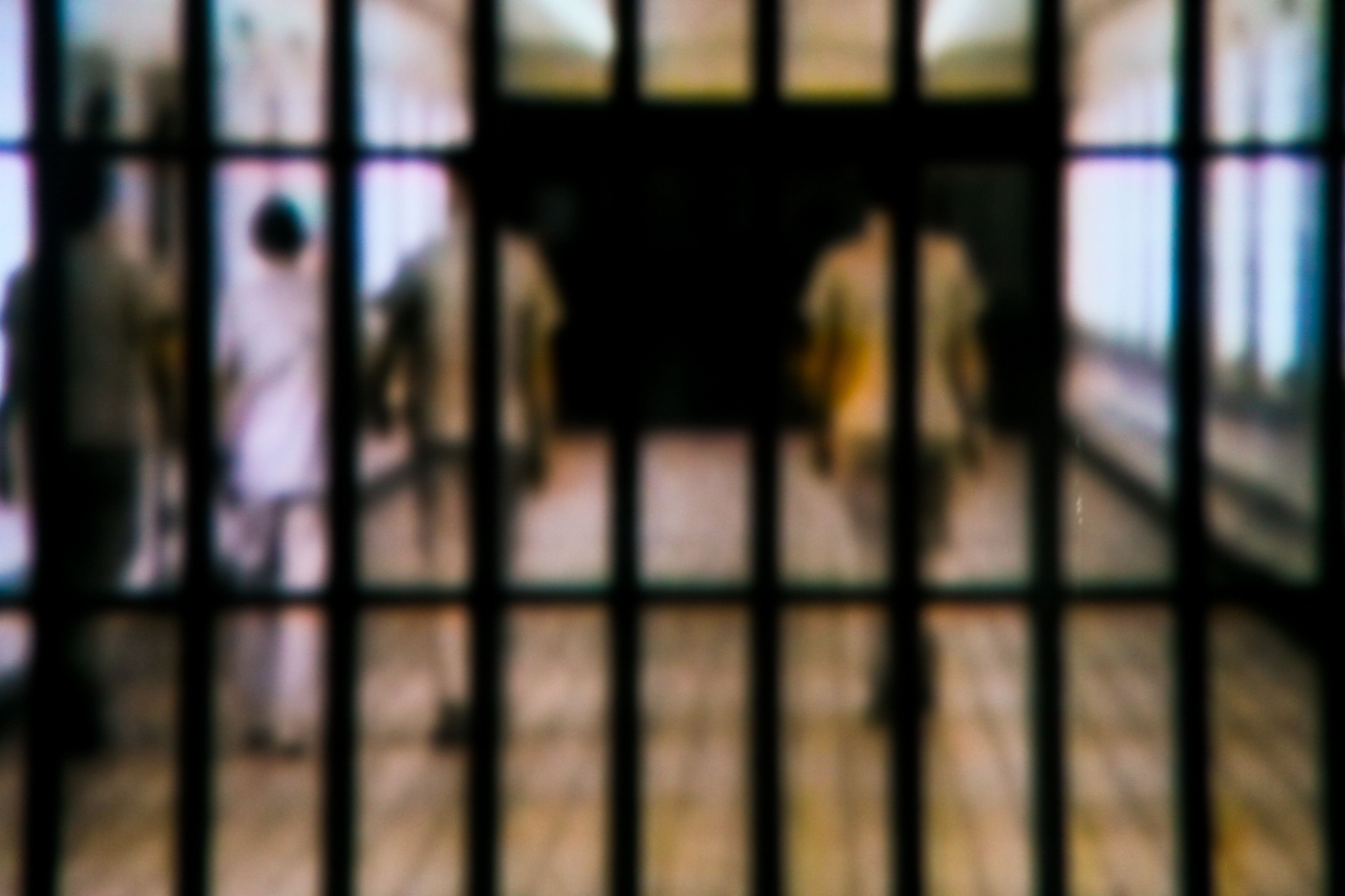 Taken this focused picture of the main entrance of a jail with people waking aware from it. Tried to capture the convict escorted by three security personal.