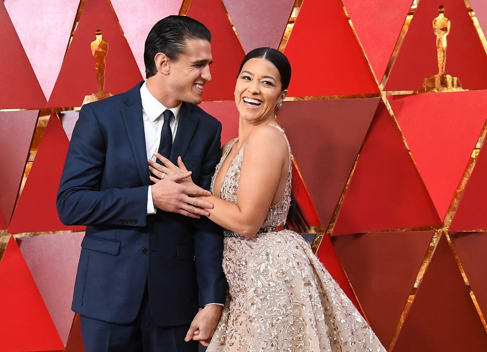 US actress Gina Rodriguez (R) and her partner Joe Locicero arrive for the 90th Annual Academy Awards on March 4, 2018, in Hollywood, California.  / AFP PHOTO / ANGELA WEISS        (Photo credit should read ANGELA WEISS/AFP/Getty Images)