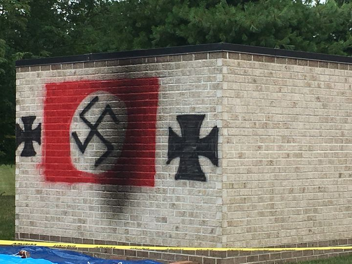A photo shows a swastika and iron crosses painted onto property belonging to Congregation Shaarey Tefilla.