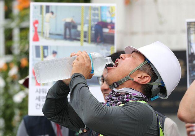 지난 24일 오전 서울 세종로 정부서울청사 앞에서 열린 '건설현장 폭염 안전규칙 이행 촉구 기자회견'에 참석한 건설노동자들이 기자회견 도중 물을 마시고