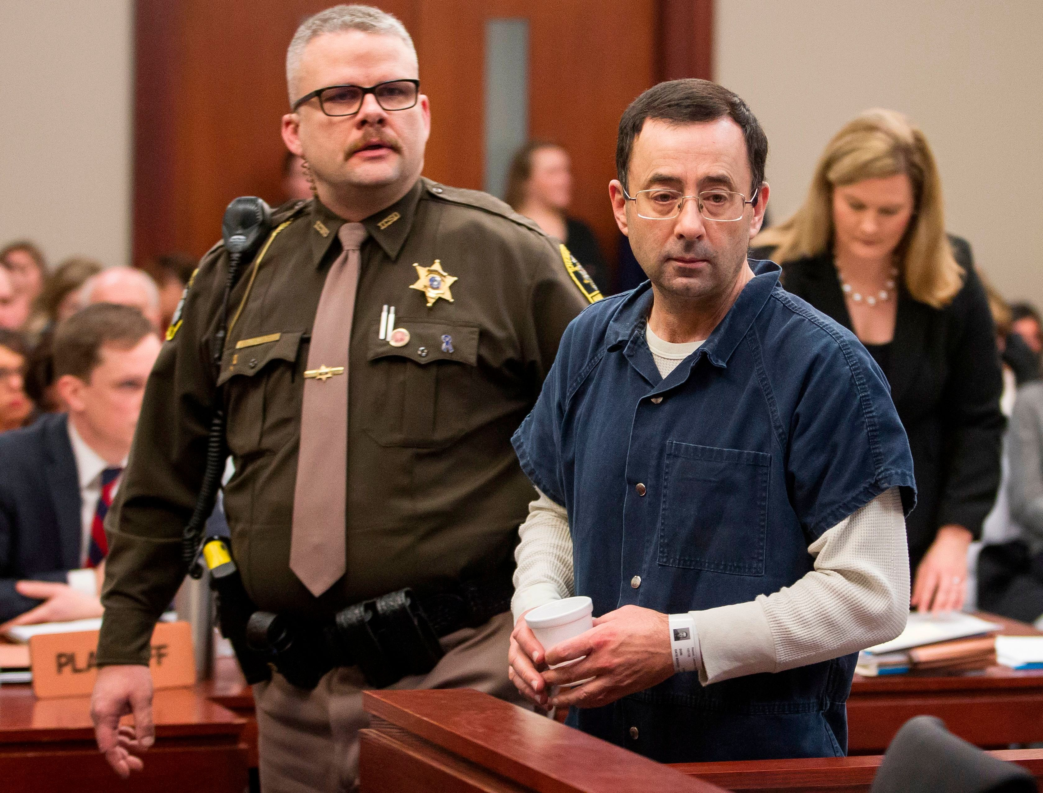 Dr. Larry Nassar is led to the witness box during his sentencing hearing in Lansing, Michigan, January 16, 2018. The former Team USA gymnastics doctor is convicted of sexual abuse charges.More than 100 athletes have accused Nassar of abuse, including members of the gold medal-winning US Olympic team.  / AFP PHOTO / Geoff Robins        (Photo credit should read GEOFF ROBINS/AFP/Getty Images)