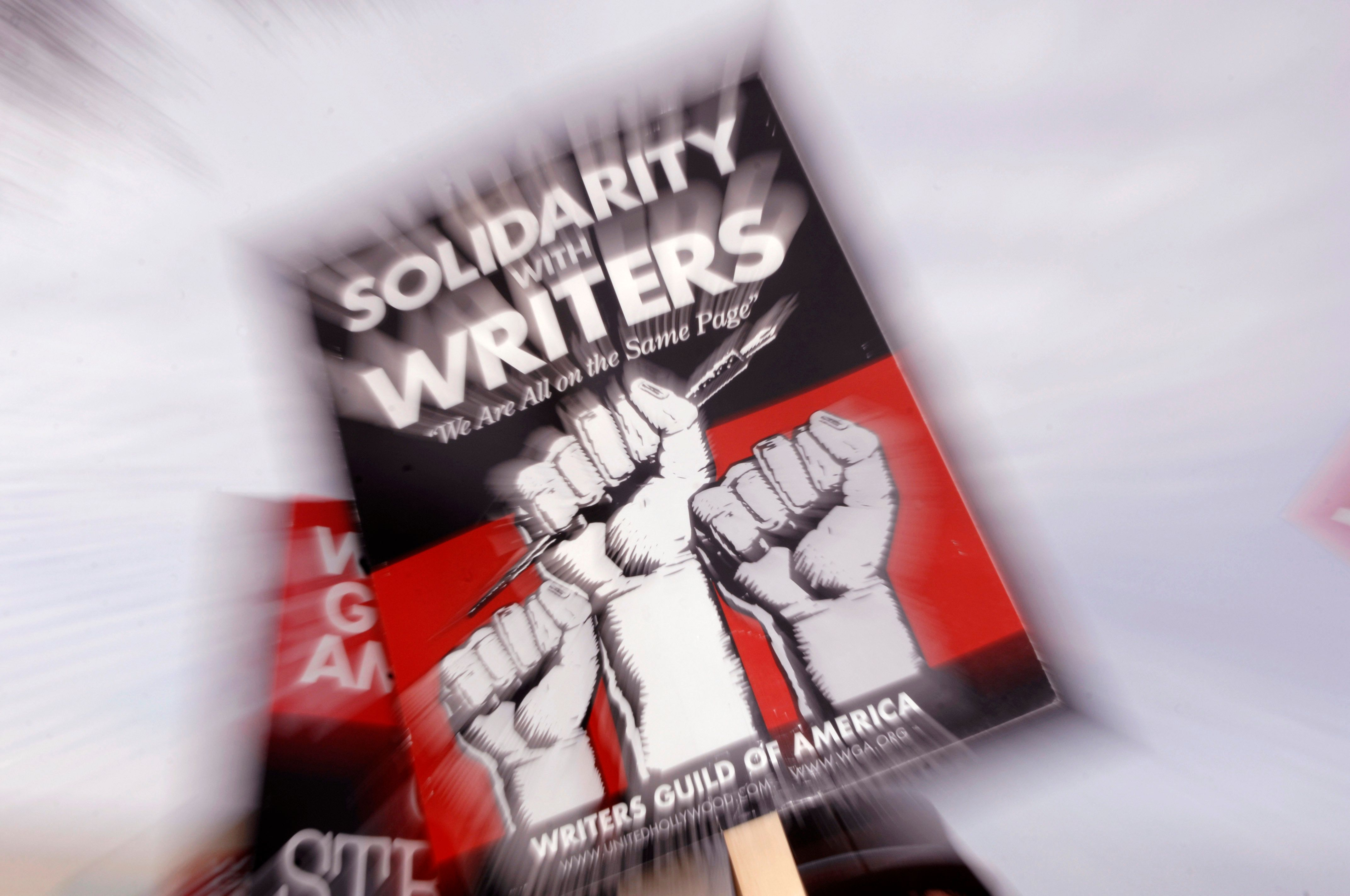 A picket sign from the Writers Guild of America is seen as members protest in front of NBC studios in Burbank, California January 2, 2008. REUTERS/Phil McCarten (UNITED STATES)