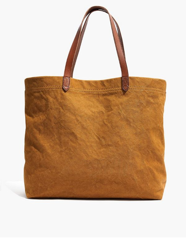 """<a href=""""https://www.madewell.com/the-canvas-transport-tote-F9414.html?dwvar_F9414_color=BL6928&cgid=accessories-bags&amp"""