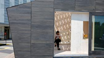 UNITED NATIONS, July 16, 2018 (Xinhua) -- A journalist sits inside an Ecological Living Module, a 22-square-meter 'tiny house', at the United Nations headquarters in New York, July 16, 2018. Developed by UN Environment and Yale University in collaboration with UN Habitat, the new eco-housing module is made to spark public discussion and new ideas on how sustainable design can provide decent, affordable housing while limiting the overuse of natural resources and climate change. (Xinhua/Li Muzi) (zxj) (Xinhua/Li Muzi via Getty Images)