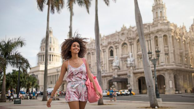 Happy woman walking on footpath. Beautiful female against Capitolio in city. She is wearing casuals.