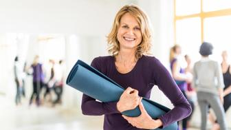Portrait of smiling mature woman holding yoga mat in gym after exercise session. Female fitness trainer in yoga class.